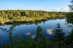 Calm lake in bright sun light with reflections of clouds and trees and blue sky. Summer in countryside royalty free stock photos