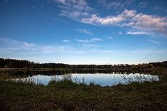 Calm lake in bright sun light with reflections of clouds and trees and blue sky. Summer in countryside royalty free stock photography