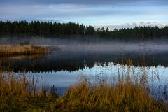Calm lake in bright sun light with reflections of clouds and trees and blue sky. Summer in countryside stock photos
