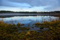 Calm lake in bright sun light with reflections of clouds and trees and blue sky. Summer in countryside stock image