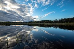 Calm lake in bright sun light with reflections of clouds and trees and blue sky. Summer in countryside royalty free stock photo