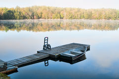 Calm lake. Dock with a fishing boat in the early morning mist in Haliburton County Ontario royalty free stock photography