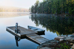 Calm lake. Dock with a fishing boat in the early morning mist in Haliburton County Ontario stock photography