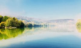 A calm lake at an early hour. Blue lake blue sky morning hour Stock Photos
