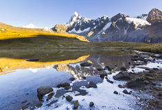 Calm lake in foot of snow-covered mountain at sunrise Royalty Free Stock Photo