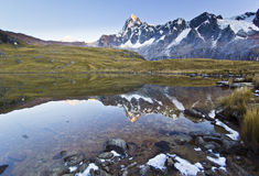 Calm lake in foot of snow-covered mountain at sunrise Stock Photography
