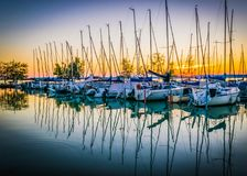 Calm lake, harbor and pier at sunset. Harbor with sailing boats and pier, dramatic clouds reflected in water, Lake Balaton, Hungary Stock Photos