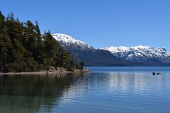 Calm Lake reflected mountains with snow. Splendid and calm day in Lake Traful, Patagonia Argentina. Beautiful landscape with mountains reflected in the lake on a royalty free stock photography