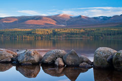 Calm lake with rocks in foreground stock image