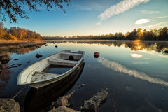 Calm lake with rowboat in autumn scenery Stock Photography