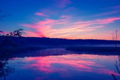 Calm lake before sunrise. Early in the morning, dawn over the lake. Calm lake before sunrise. A misty morning, a rural landscape, a desert, a mystical feeling Stock Image