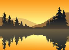 Calm Lake at Sunset. Casting an orange glow the sun sets behind the hills of a calm  lake Royalty Free Stock Photo