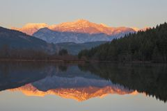 Calm lake at sunset with snowcapped mountains in background royalty free stock images