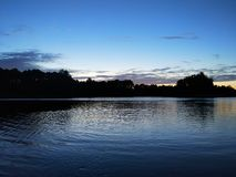 Lake surface at evening in Latvia, East Europe. Landscape with water and forest. Royalty Free Stock Images