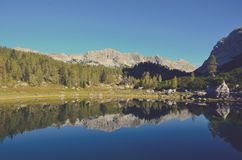Calm Lake Surface Mirroring Forest Trees and Mountain Ranges at Daytime Royalty Free Stock Photography