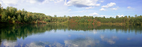 Calm lake surrounded by trees panorama Stock Image