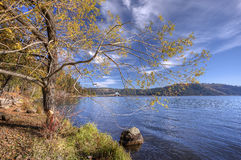 Calm lake under blue sky. Stock Photos