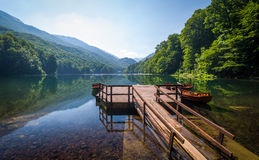 Calm lake water with reflections of forest on the hills and beautiful old wooden pier Royalty Free Stock Images