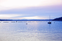 Calm lake waters  at dusk with empty sailboat Royalty Free Stock Photography
