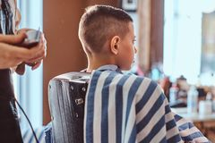 Calm little school boy is preparing for the school at trendy barbershop. With mature hairdresser stock image
