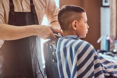 Calm little school boy is preparing for the school at trendy barbershop. With mature hairdresser royalty free stock photo