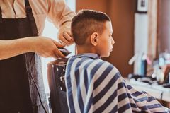Calm little school boy is preparing for the school at trendy barbershop. With mature hairdresser royalty free stock photography