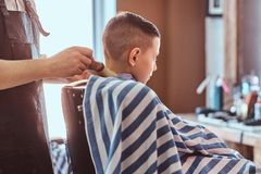 Calm little school boy is preparing for the school at trendy barbershop. With mature hairdresser stock photo