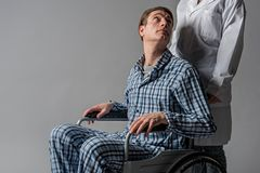 Serene disabled man staring at nurse stock photos