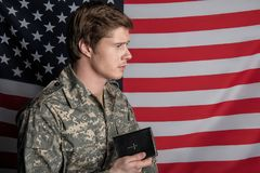 Calm male soldier having book in hand stock images