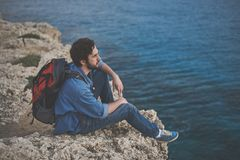 Serene young woman looking at water on cliff. Calm male tourist is sitting on the rock and enjoying the sea view. He is carrying rucksack on back Stock Images