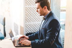 Calm male typing on keyboard in apartment. Side view serene bristled businessman using laptop while working at table in room Royalty Free Stock Image