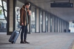 Calm male watching at wristwatch. What time is it. Full length side view serious man looking at modern watch while keeping big suitcase. He waiting for train Stock Image
