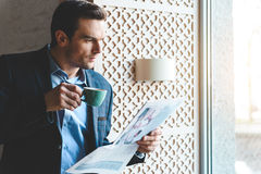 Calm man drinking mug of beverage. Serene bristled male tasting cup of appetizing coffee while reading newspaper. He standing near window Stock Photography