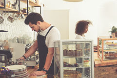 Calm man preparing tasty cup of hot beverage. Serene male barista making delicious americano with coffee mill in comfortable cafe. Happy women standing at Stock Photo