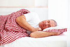 Calm mature man sleep in bed. In bright room Stock Photography