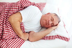 Calm mature man sleeps in bed. In bright room Stock Images