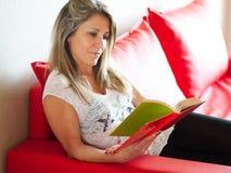 Calm mature woman enjoying a book on sofa Stock Image