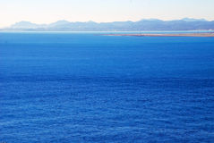 Calm Mediterranean Sea on a sunny day. Seen in the distance on the background of the mountainous coast Royalty Free Stock Photography