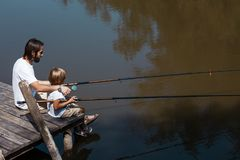 Calm men`s world. Father and little son, both in the white t shirts, are sitting on the wooden bridge and fishing. stock image