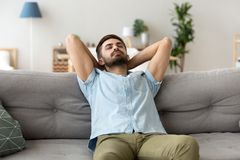 Calm man relaxing on sofa hands over head. Calm millennial man relax on cozy couch hands over head sleeping or taking nap, peaceful male lying on sofa with eyes royalty free stock photography