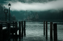 Calm misty lake at down. A calm, misty lake at down as seen from pier with lantern and clock. A lone island shines from the fog in the distance - at Koenigssee Stock Images