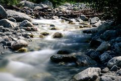 The calm of a mountain creek. A mountain creek in the California foothills. a man made wooden structure in the background Royalty Free Stock Image