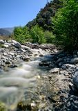 The calm of a mountain creek. A mountain creek in the California foothills. a man made wooden structure in the background Stock Photo
