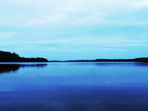 Calm mysterious lake. Blue calm lake in Masuria Stock Photo