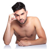 Calm naked pensive man looking at the camera. While sitting on white background Royalty Free Stock Image