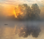 Calm. Nice quiet morning on a lake with an island and the sun coming up in the background Royalty Free Stock Photography