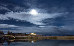 A calm night by the lake. A calm night by a lake in the city of Reykjavik, Iceland, with the full moon hiding behind clouds royalty free stock photo