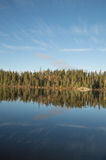 Calm Northern Ontario lake in early morning with reflected cloud Stock Image