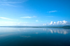 Calm ocean in Gulfo Dulce, Costa Rica. Calm ocean in Gulfo Dulce with a beautiful reflection of the clouds & the coastline in the distance, Costa Rica stock photo