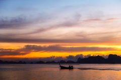 Calm ocean & open sea with twilight sky & silhouette fishing boat. Calm ocean in open sea with twilight sky at the evening on dark clouds and mountain background stock photo